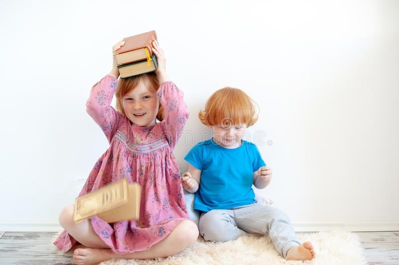 The girl hugs her favorite book. The redhead girl hugs her favorite book stock images