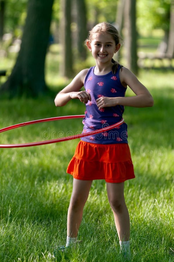 Girl Hula Hooping. A smiling 9 year old blond girl hula hooping with in park stock photos