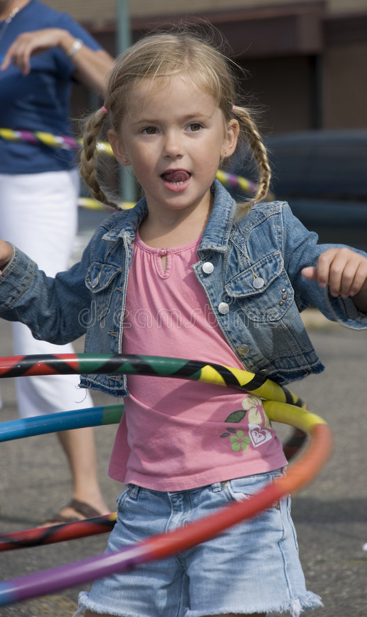 Girl Hula Hooping. Smiling 4 year old blond girl hula hooping with two hoops at once outdoors royalty free stock photos