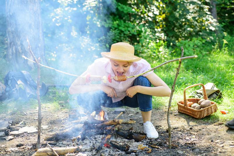 Girl hungry tourist can not wait when food will be roasted. Woman in straw hat try to bite sausage on stick. Girl eats royalty free stock photo