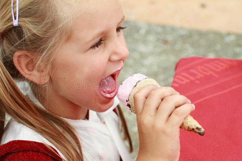 Girl with ice-cream. Little girl in red dress with ice-cream royalty free stock image