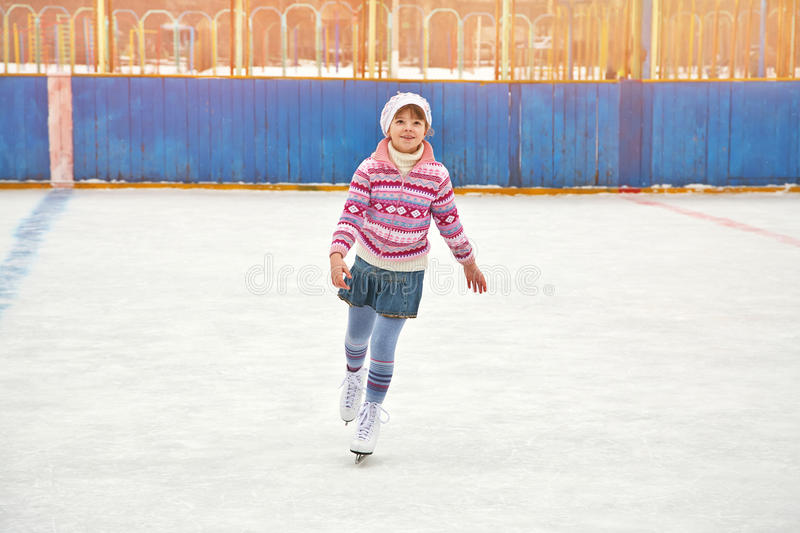 Girl ice skating on rink. Cute little girl in a hat and a sweater ice skating. child winter outdoors on ice rink royalty free stock photography