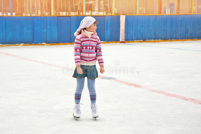 Girl ice skating on rink. Cute little girl in a hat and a sweater ice skating. child winter outdoors on ice rink royalty free stock images