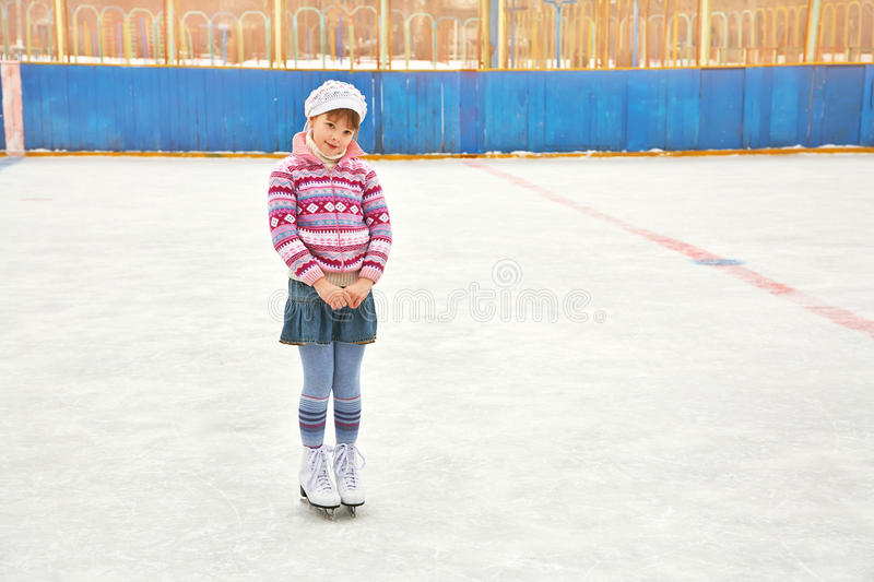 Girl ice skating on rink. Cute little girl in a hat and a sweater ice skating. child winter outdoors on ice rink stock photos