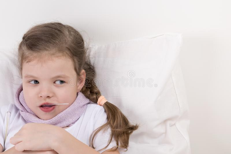 Girl is ill and looks at the right, with a spoonful of medication, lying in bed stock photography