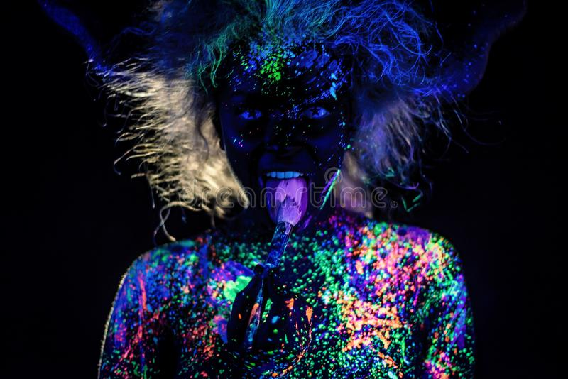The girl in the image of the devil, contact lenses and horns. Woman paints her tongue in ultraviolet paint. fluorescent. Powder. Body art glowing in ultraviolet stock images