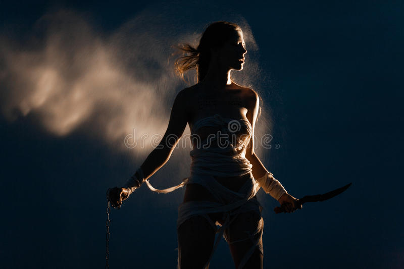 Girl in image of Egyptian mummy stands with metal chain and knife in her hands. stock photo