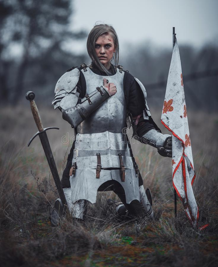 Girl in image of Jeanne d`Arc in armor kneels with flag in her hands and sword on meadow. royalty free stock photography