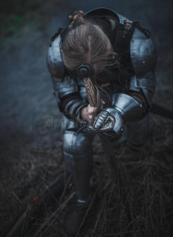 Girl in image of Jeanne d`Arc in armor and with sword in her hands kneels against background of dry grass. stock photos