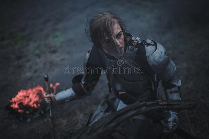 Girl in image of Jeanne d`Arc in armor and with sword in her hands kneels against background of fire and smoke. stock images