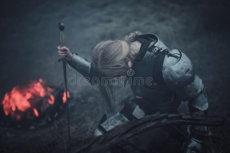 Girl in image of Jeanne d`Arc in armor and with sword in her hands kneels against background of fire and smoke. stock photos