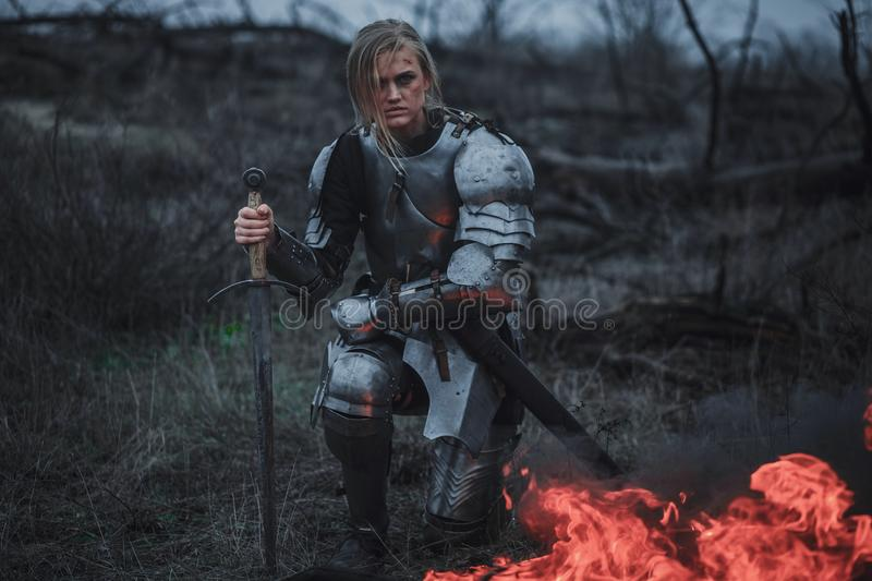 Girl in image of Jeanne d`Arc in armor and with sword in her hands kneels against background of fire and smoke. stock image