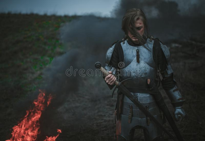Girl in image of Jeanne d`Arc in armor and with sword in her hands stands against background of fire and smoke. stock photos