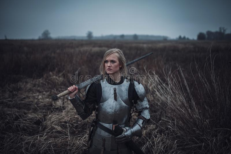Girl in image of Jeanne d`Arc in armor and with sword in her hands stands on meadow. Closeup. royalty free stock photography