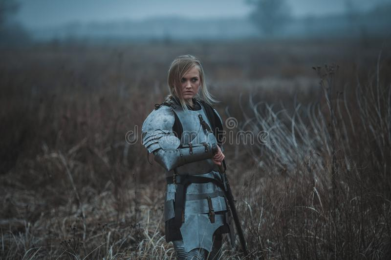 Girl in image of Jeanne d`Arc in armor and with sword in her hands stands on meadow. Back view. royalty free stock image