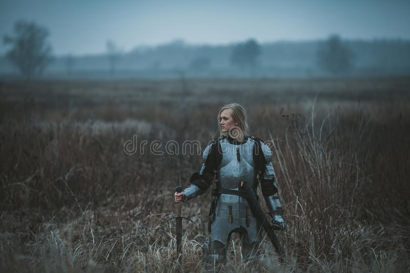 Girl in image of Jeanne d`Arc in armor and with sword in her hands stands on meadow. Back view. stock photo
