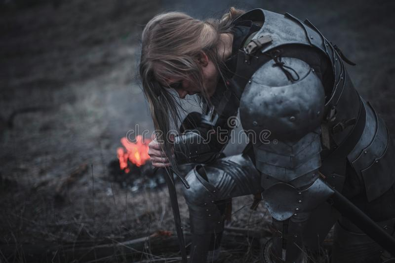 Girl in image of Jeanne d`Arc kneels in armor and with sword in her hands against background of fire and smoke. royalty free stock photos