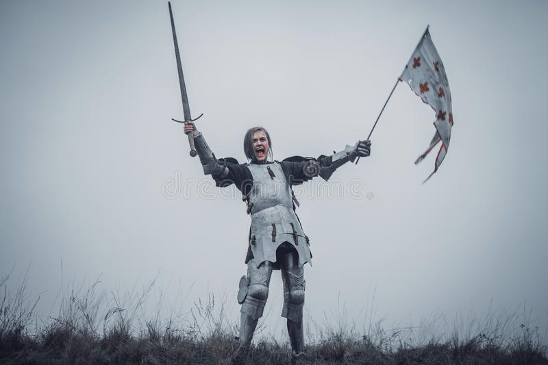 Girl in image of Jeanne d`Arc stands in armor and issues battle cry with sword raised up and flag in her hands. stock image