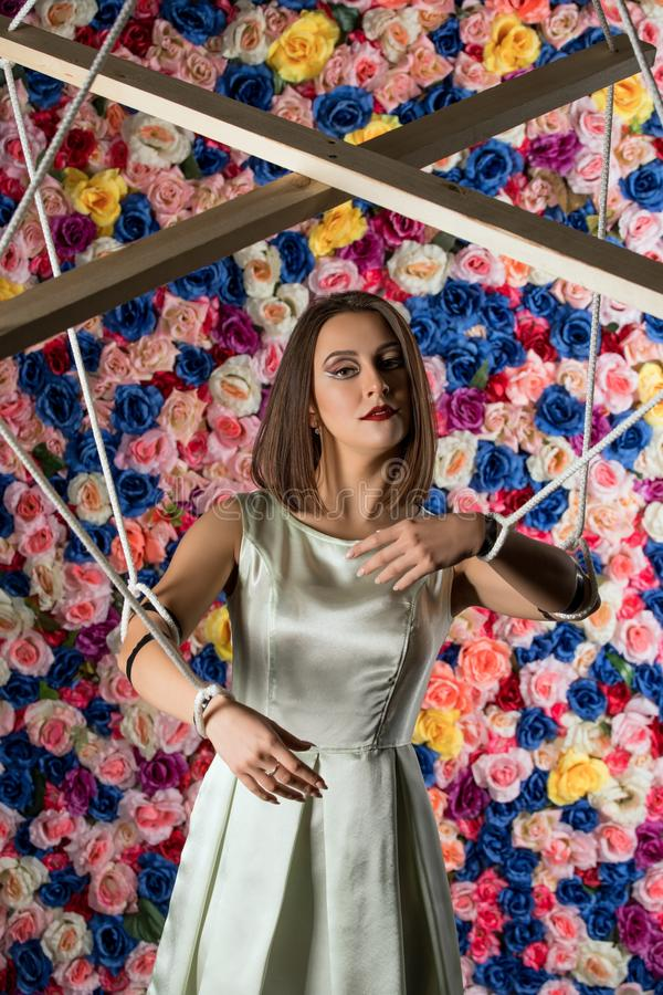 Girl in the image of marionette on flower wall royalty free stock image