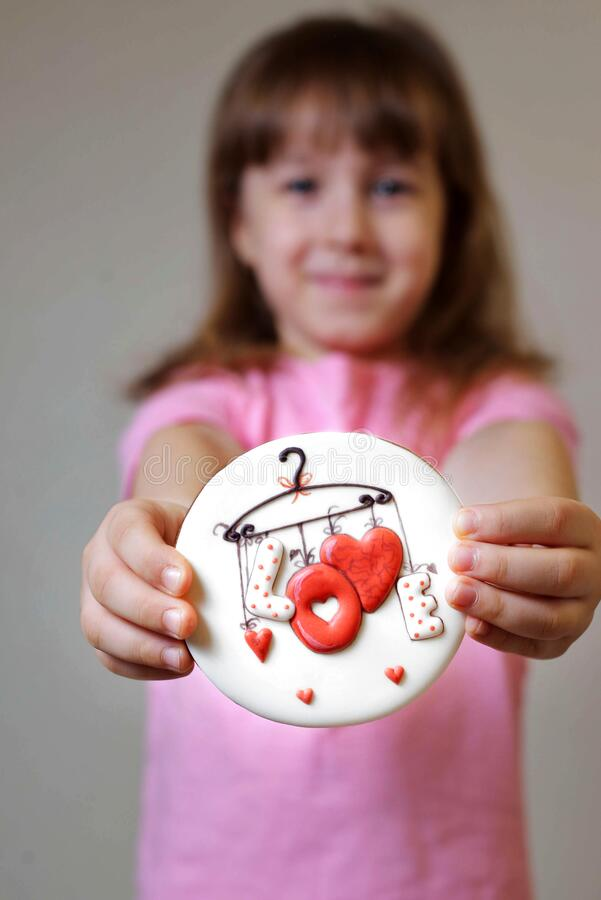 Free Girl In A Pink T-shirt Holds A Gingerbread Valentine Card. Gift For Valentine`s Day. Stock Photos - 209657403