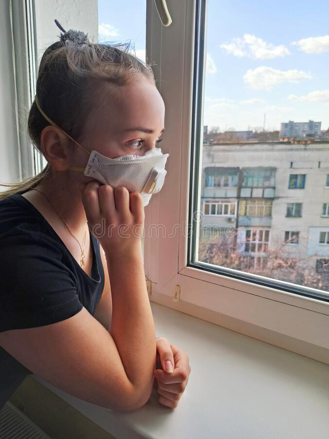 Free Girl In Protective Mask Looking Sadly Out The Window During Quarantine Stock Image - 178666331