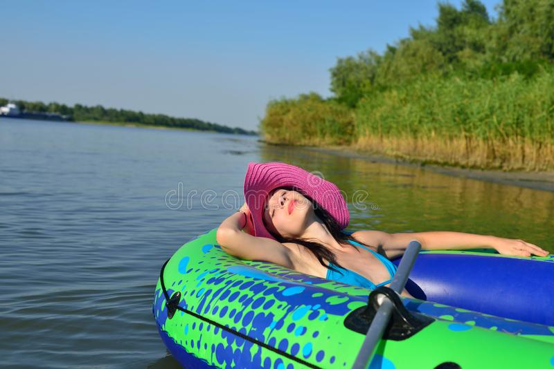 Girl on an inflatable boat in a hat. Girl resting on the river in an inflatable boat stock photo