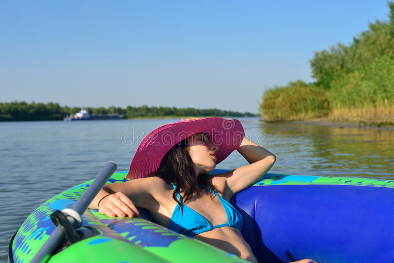 Girl on an inflatable boat in a hat. Girl resting on the river in an inflatable boat stock photography