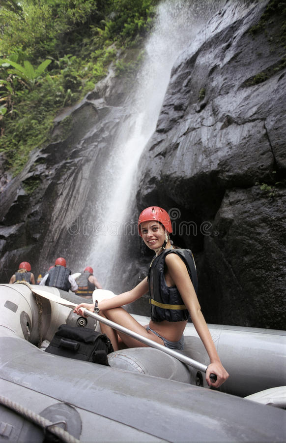 The girl an inflatable boat at waterfalls. The girl with an oar in an inflatable boat at waterfalls. Rafting Ayung River. Bali, Indonesia stock images