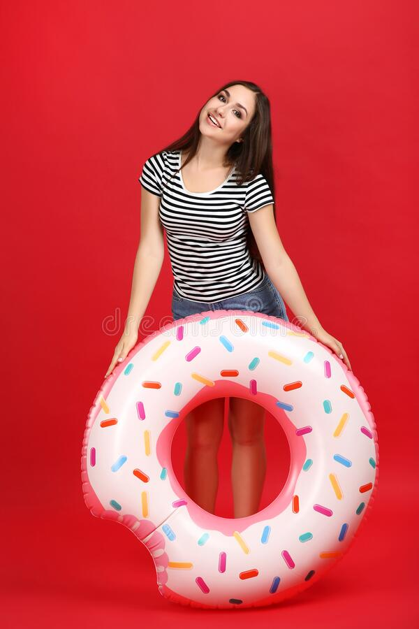 Girl with inflatable donut. Young girl with inflatable donut on red background royalty free stock photography