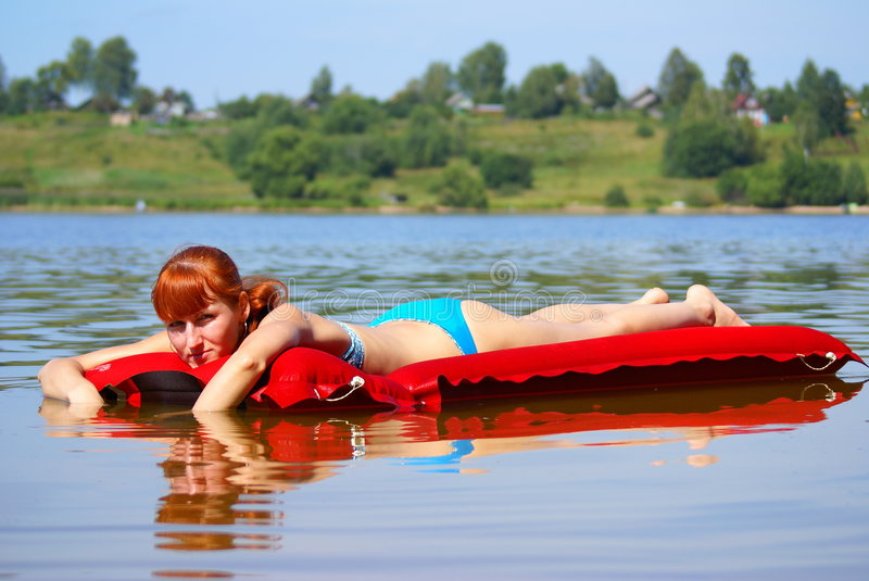 Girl on an inflatable mattress stock images