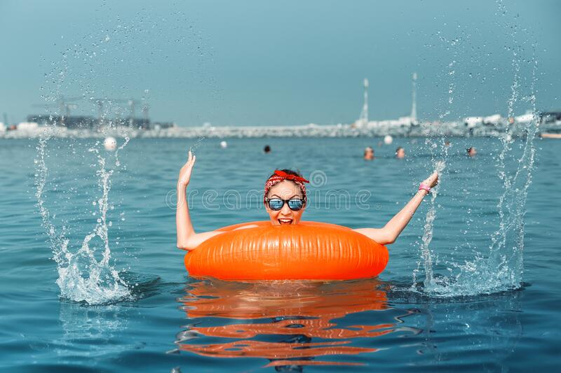 Girl with inflatable ring having fun and swimming at a popular sea resort. Vacation and safety concept. Happy Asian girl with inflatable ring having fun and stock images