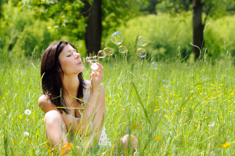 Girl Inflating Soap Bubbles Stock Photo
