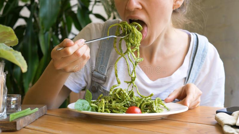 Girl inputs fresh raw vegetable salad on silver fork stock photo