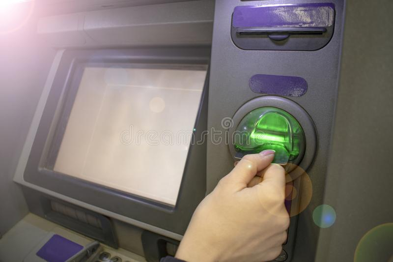 The girl inserts a card in the ATM. Close-up. The concept of deposits and savings.  royalty free stock photography