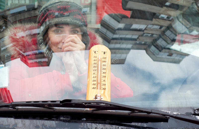 Girl inside the car with a thermometer on the wind screen royalty free stock images