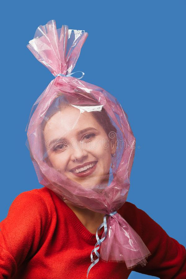 Girl inside wrapper. Fun girl with head inside candy wrapper on blue background royalty free stock image