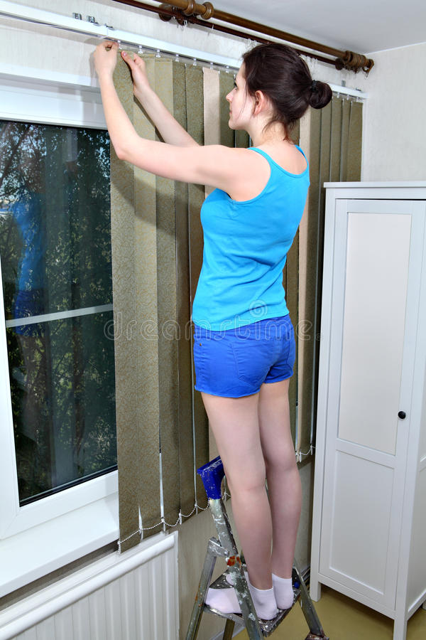 Girl installs dense fabric vertical blinds, click into place slats. Girl attach slats, vertical fabric blinds to rail stock photos