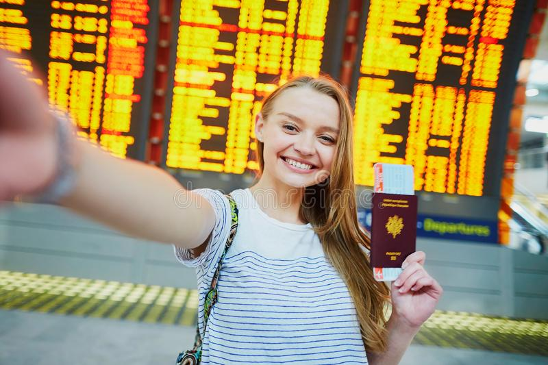 Girl in international airport, taking funny selfie with passport and boarding pass near flight information board. Beautiful young tourist girl in international royalty free stock photos