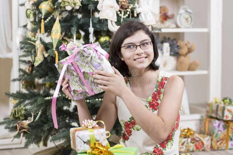 Girl Is Intrigued With Christmas Gift Stock Images