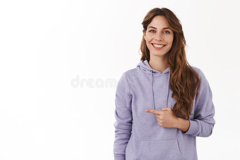 Girl introducing girlfriend friends pointing left index fingers smiling silly lovely modest standing white background royalty free stock images