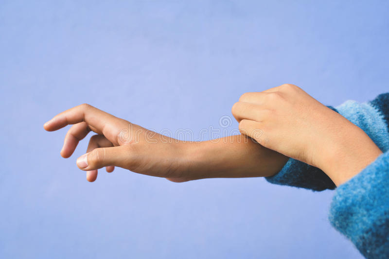 A girl itch arm. On blue background stock photography