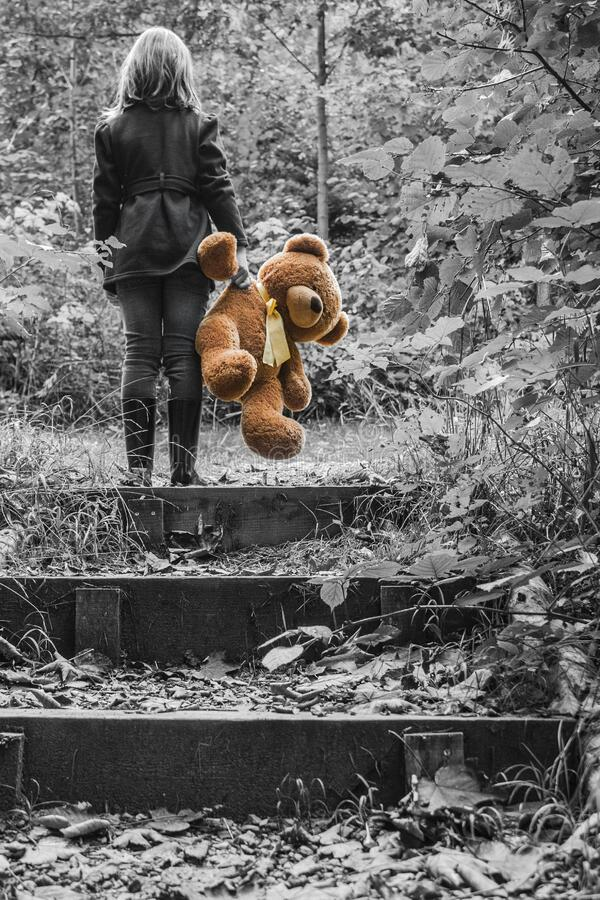Girl in Jacket Carrying Brown Bear Plush Toy Selective Color Photo stock image