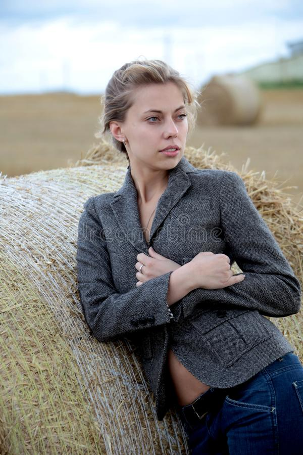 Girl in the jacket in the field royalty free stock photo