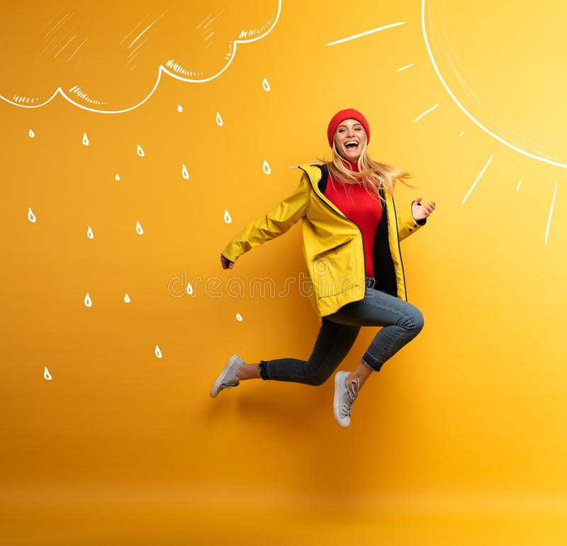 Girl with jacket jumps to the sun from the rainy weather. Joyful expression. Yellow background royalty free stock photo