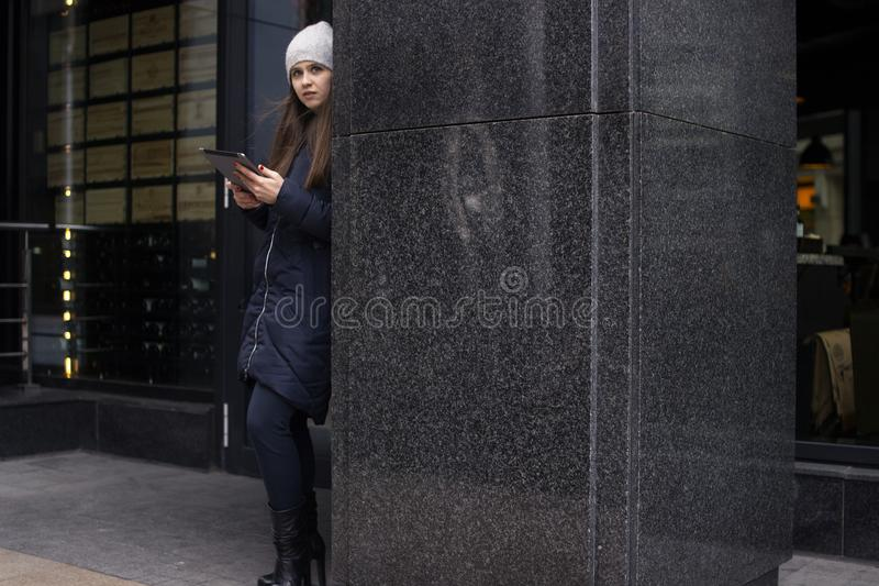 A girl in a jacket stands near the wall stock photos