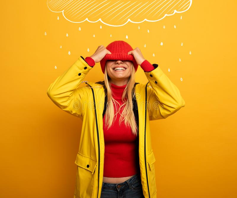 Girl with jacket on yellow background covers her face with her hat for the weather stock images