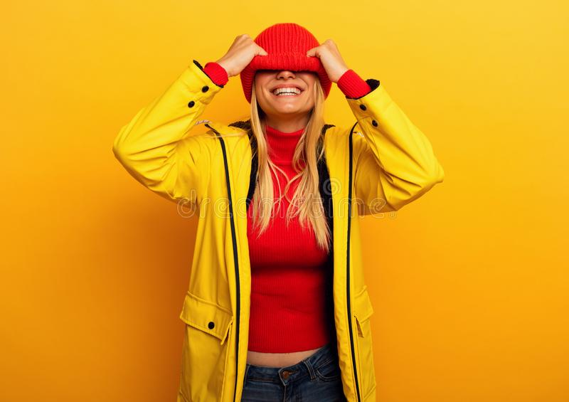 Girl with jacket on yellow background covers her face with her hat for the weather royalty free stock image