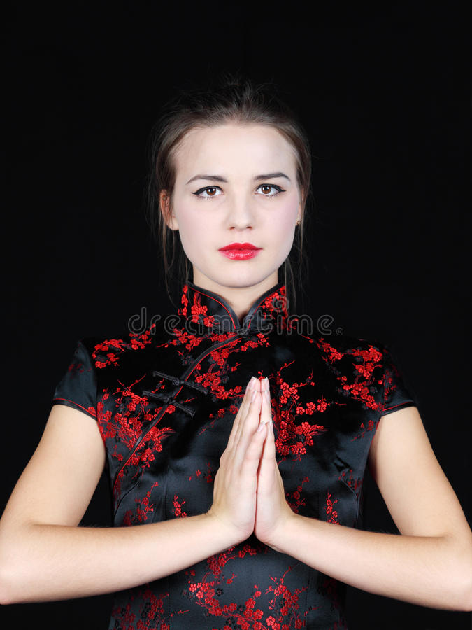 Girl in Japanese silk blouse puts hands before chest stock photography