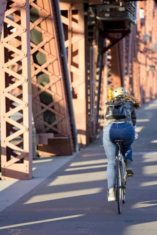 Girl in jeans and backpack riding bike over the bridge stock image