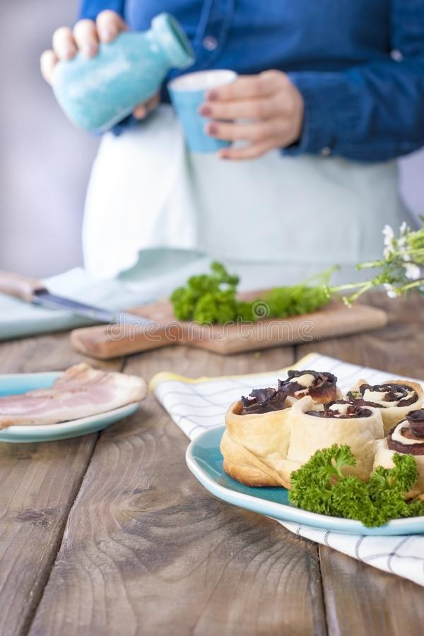 A girl in jeans clothes prepares a lunch of bacon and dough, with fresh herbs. Brown wooden background. Kramic dishes of blue cet. royalty free stock image